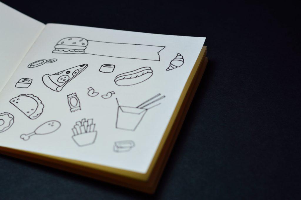 An open sketchbook full of drawings of food.